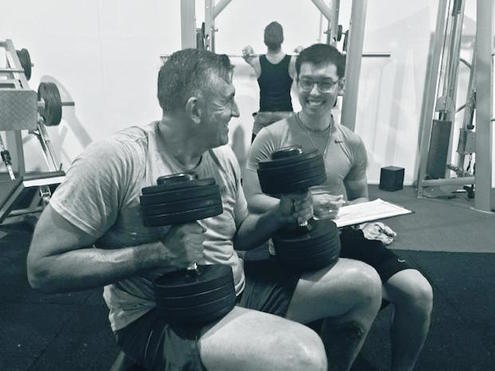 Personal Trainer Jimmy with client holding dumbbells